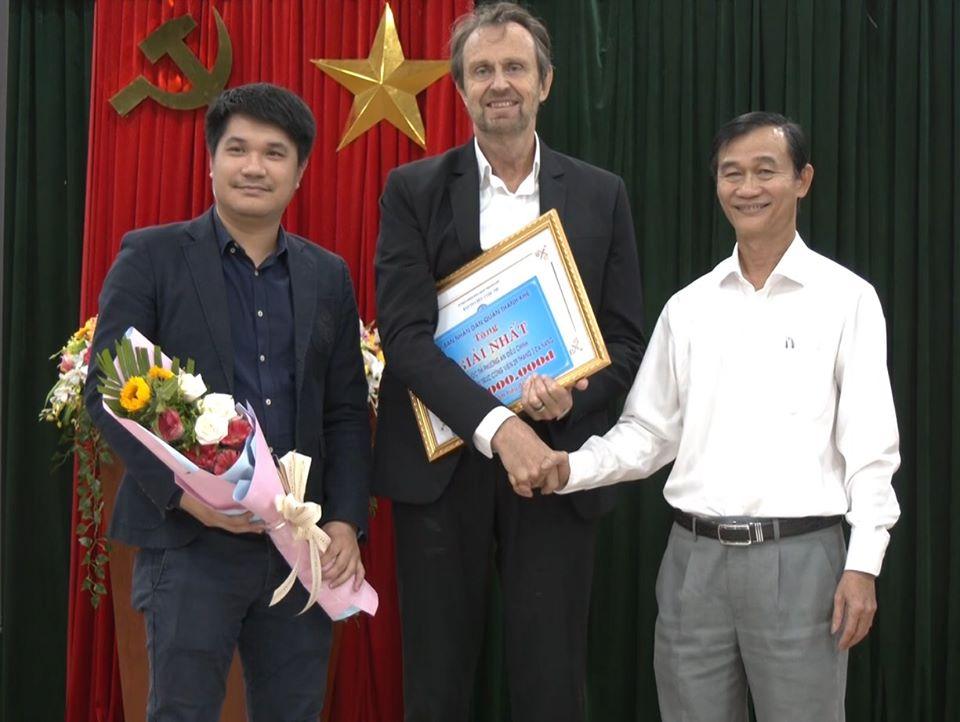Chủ tịch UBND quận Thanh Khê Nguyễn Văn Tĩnh (phải) trao giải nhất và giải cộng đồng cho Công ty StudioMilou Singapore